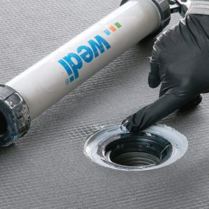 Joint sealant goes below the flange, and a threaded collar pulls it tight. More sealant goes over the top.