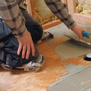 Apply a notched coat of thinset mortar to the back of the pan and the subfloor.