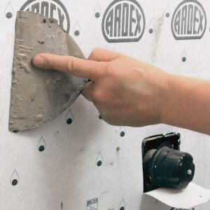 Collapse the ridges. Use a flat trowel to evacuate all of the air bubbles and flatten the thinset ridges to get adhesion across 100% of the surface. Run your hands over it last to feel for any lingering air pockets, and push those to the edge with the trowel.