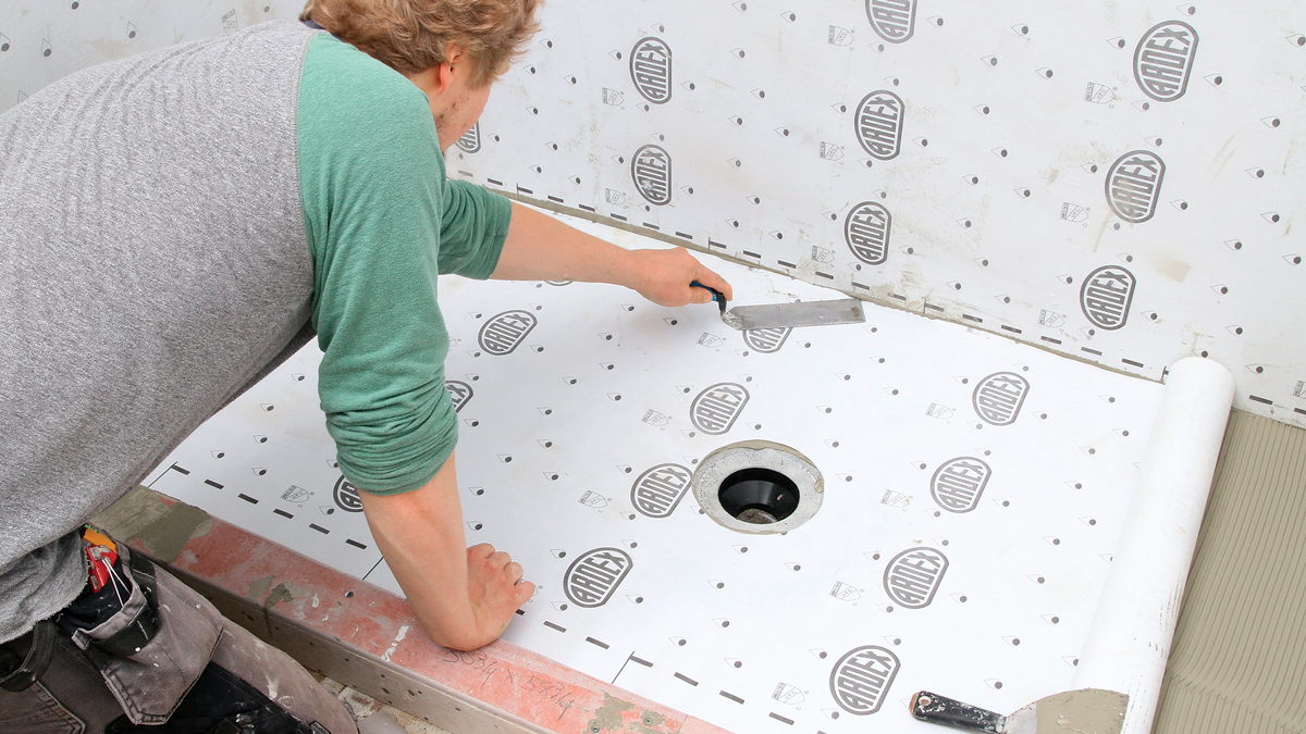 Pan membrane goes down the same way. The sheet seals around a wide, sloped drain flange (designed for sheet membranes), which glues directly onto the ABS plumbing pipe. After collapsing the ridges, eliminating bumps, and evacuating bubbles, run your hands over the sheet to check for a 100% bond across the entire surface.