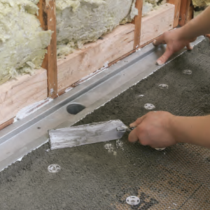 I'm using a Laticrete linear drain here, setting it in the dry-pack mud-bed shower pan before installing the bottom piece of foamboard over its back edge.