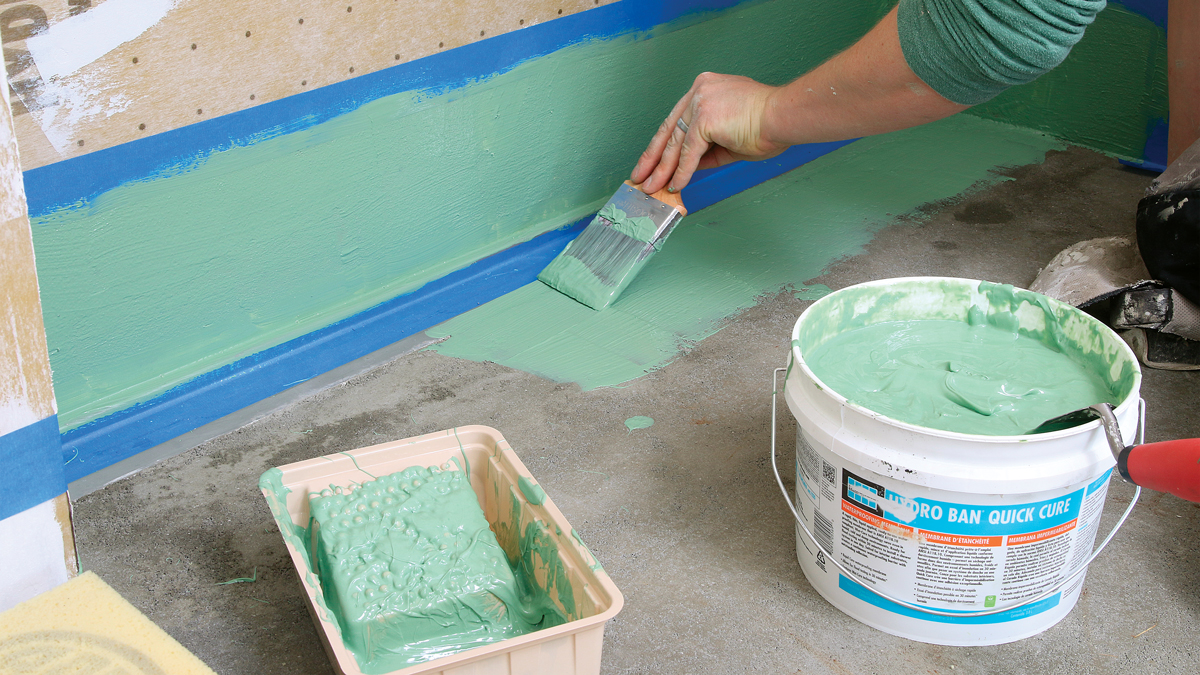 Liquid-applied membrane is a versatile tool. After finishing the mud-bed pan, I waterproof the drain area with two coats of a quick-curing liquid membrane from Laticrete, building a seal 6 in. up and out in all directions.