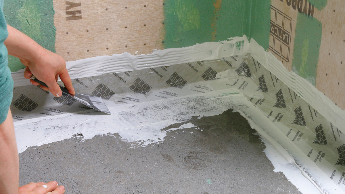Fabric banding at the edges. To prevent cracks in the tile and grout, the critical joints around the pan get a fabric banding. Like the liquid membrane, this is designed to go over damp concrete for the best bond, so you might have to dampen the mud bed before installing it.