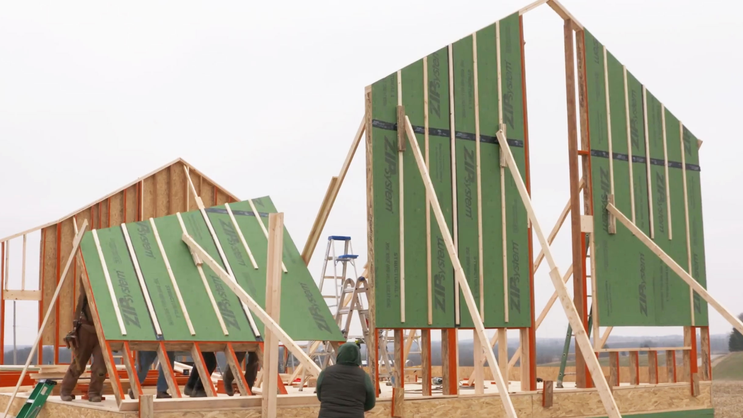 A tip raises a wall covered in green ZIP sheathing