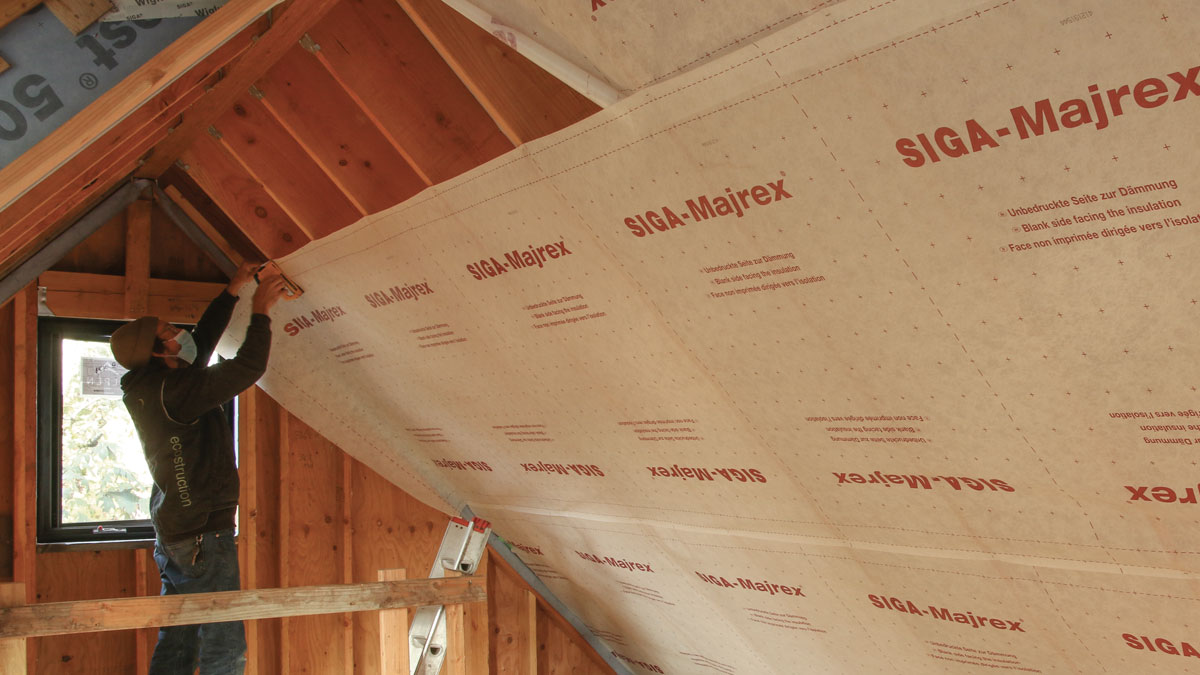 Vapor-permeable air barrier. The Siga Majrex is rolled out and cut on the floor, and then lifted up and installed perpendicular to the rafters.