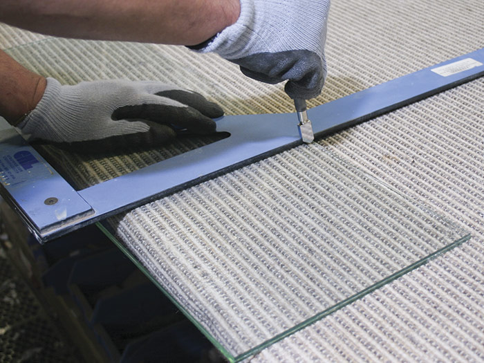 Holding a glass cutter perpendicular to the pane, pull it evenly along a straightedge
