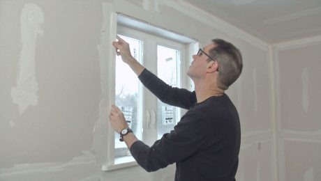 Myron applies a drywall bead to the side of a window
