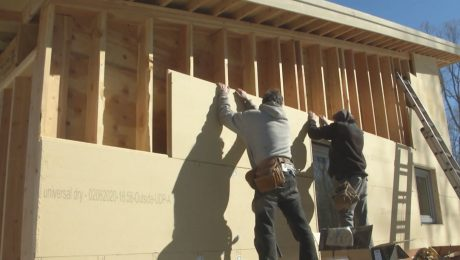 Workers intalling wood fiber insulation