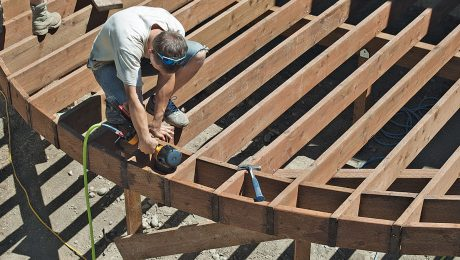 A person installing a border on a curved deck