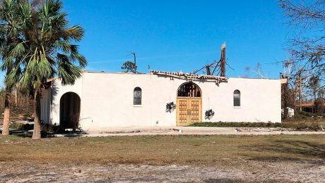 A partially destroyed church against a blue sky and palm trees
