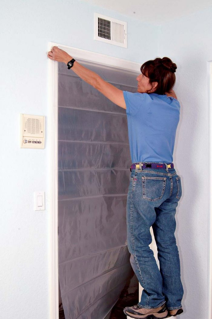 Taping plastic sheeting over a doorway keeps out dust