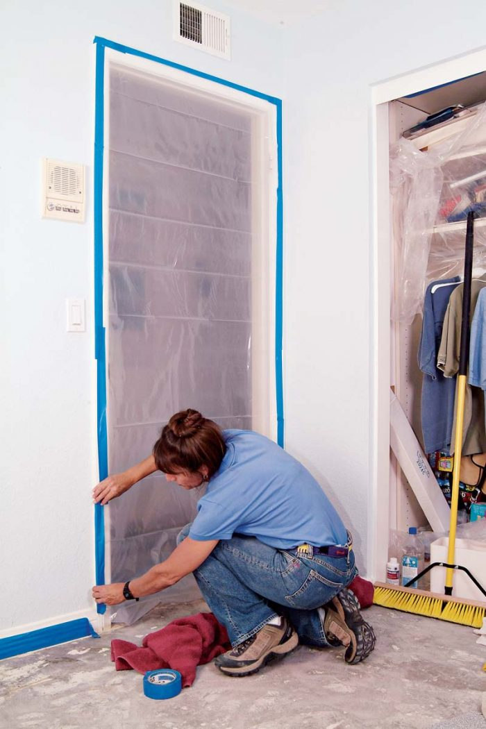 Tape plastic sheeting to the door frame using blue painter's tape.