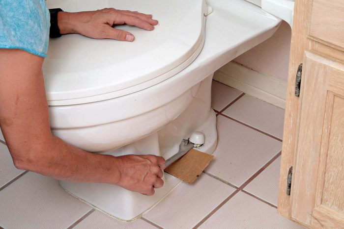 Use a piece of cardboard to protect the toilet as you pop off the bolt caps.