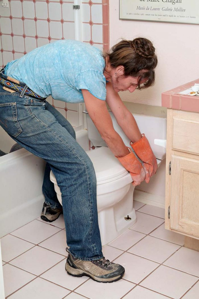 Rock the toilet side to side carefully to loosen the seal, grout, and caulking.