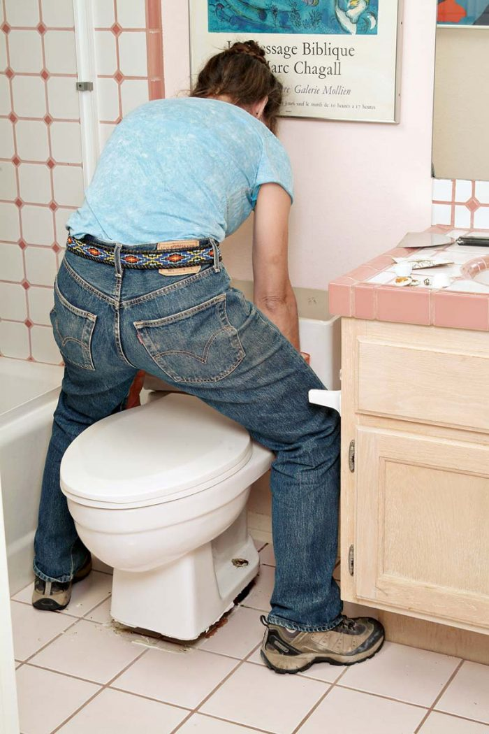Straddle the toilet and lift straight up and off the sewer flange and bolts.