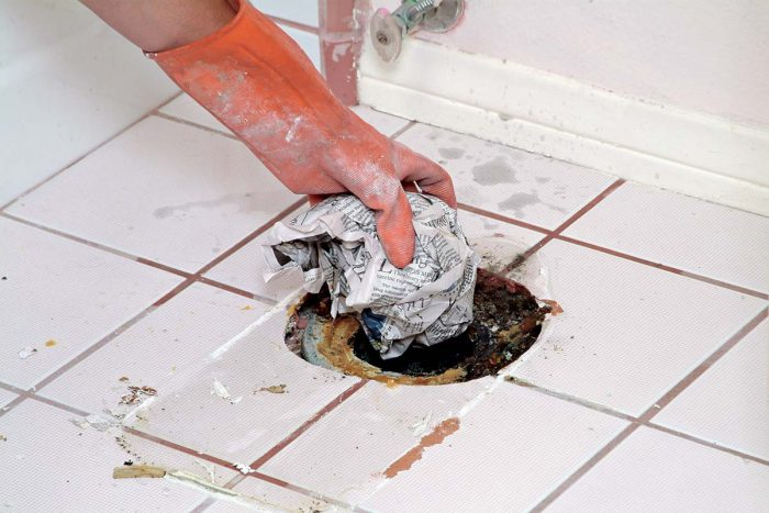 Plug the sewer line with a wad of newspaper to prevent the escape of gases.