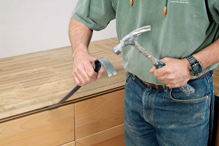 Insert a prybar under the countertop and lift it from the cabinet frames.