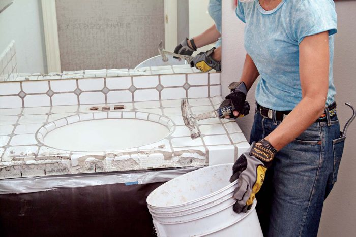 Hammer off the edge trim tiles into a bucket to start your countertop demolition.