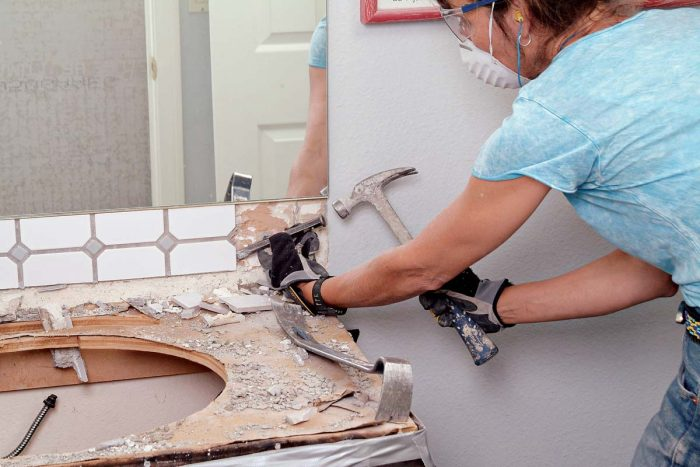 Carefully remove a tiled backsplash by starting at the edge, then work inward.