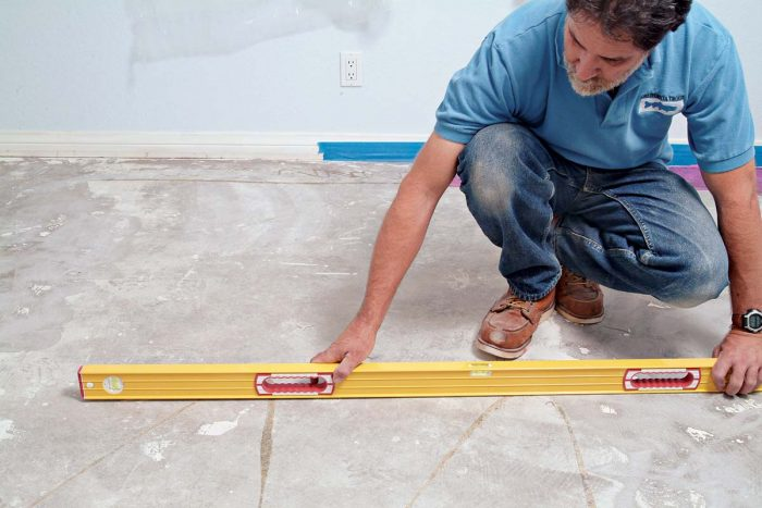 Use your level to check the concrete slab for hills or valleys before you start any tile work.