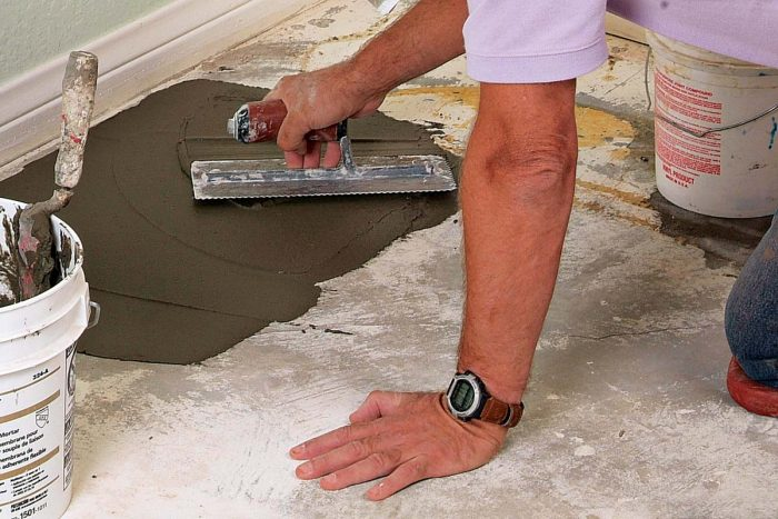Fill and feather low spots with thinset. Spread with a flat trowel, then smooth and check with a straightedge.