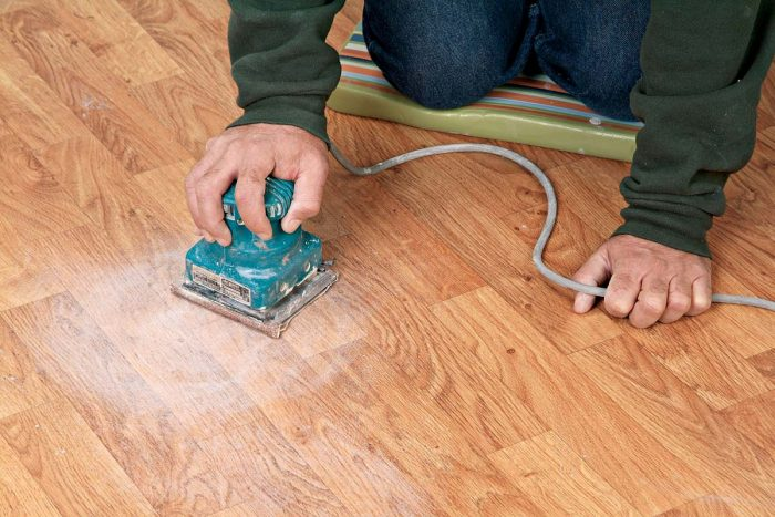 """Sanding a vinyl floor with 60-grit sandpaper will give it the """"tooth"""" it needs for adhering backerboard to it with thinset."""