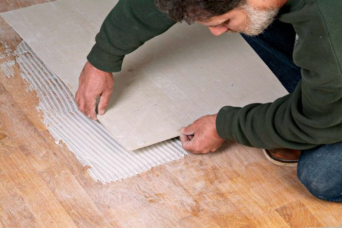 Comb the thinset and lay the backerboard over the sanded vinyl floor.