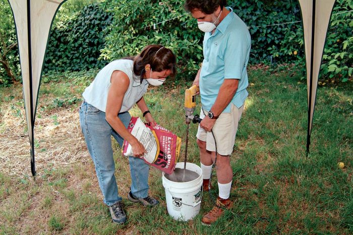 Pour dry compound into the water-filled bucket slowly. Mix with a low-speed drill.