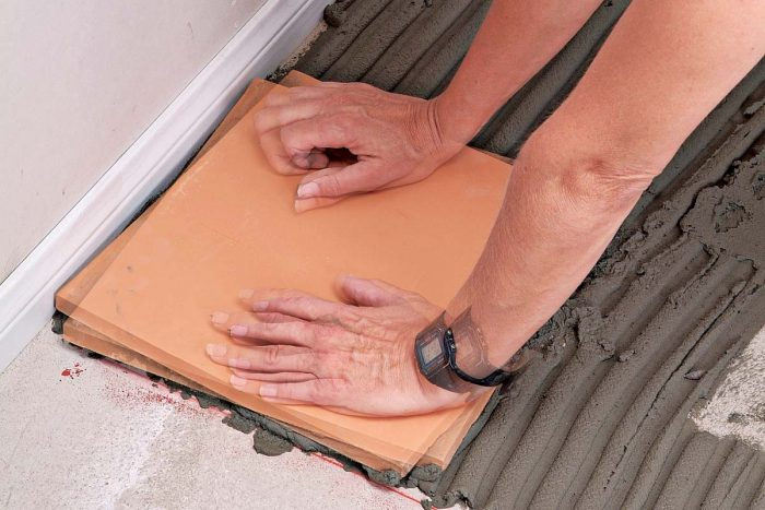 Setting each tile with a back and forth twisting motion ensures that it's well embedded in the thinset.