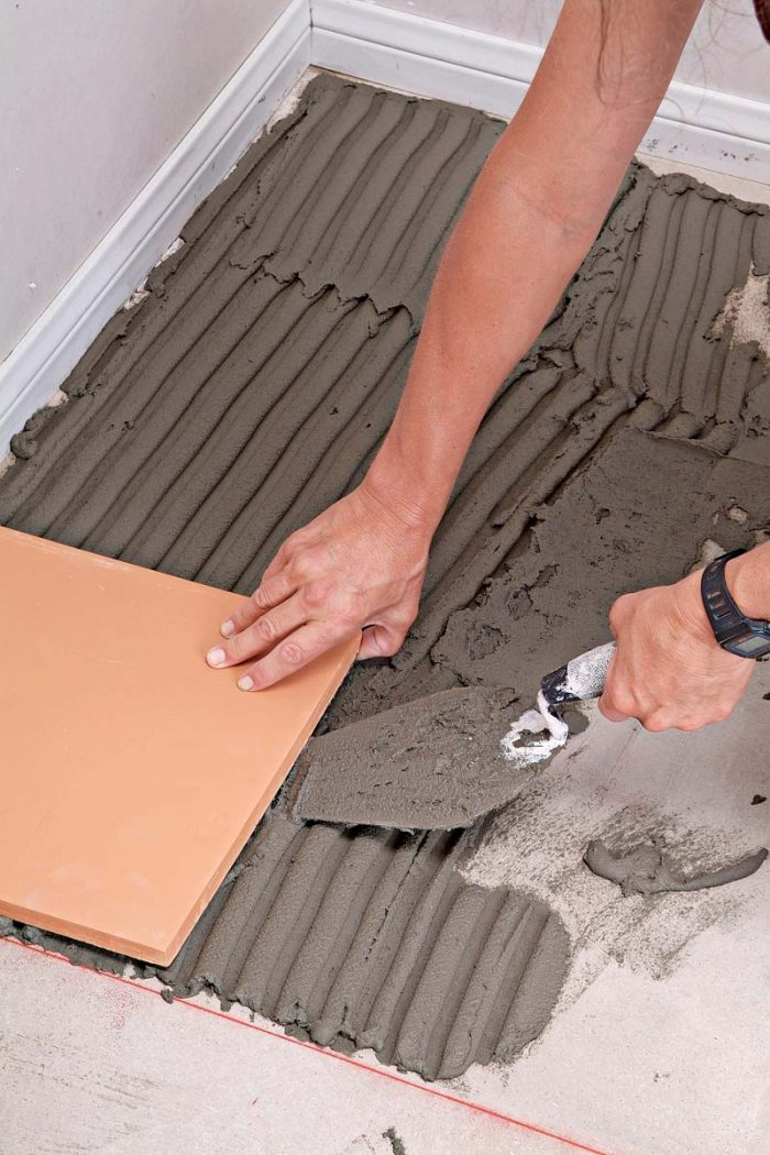 Use a trowel or margin trowel to lift tiles that aren't well seated in the thinset.