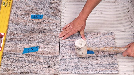 Tapping the tile with a mallet embeds it into the thinset.