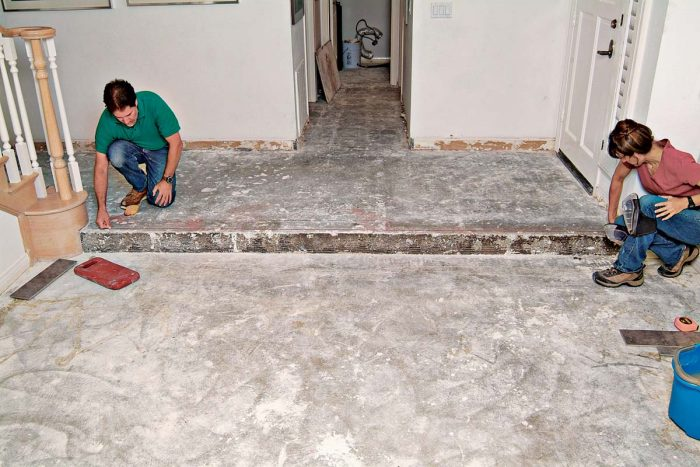 A long chalkline provides a reference line for setting the first row of entry tiles and the bullnose trim to be set on the edge of the step.