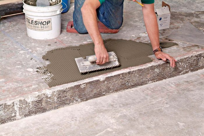 Thinset is spread and combed in the area where the first tile is to be set, at the intersection of the chalklines.