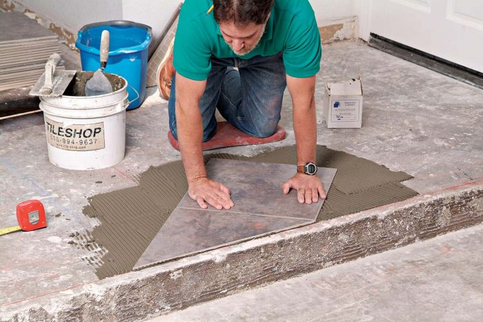 Subsequent tiles are set aligned to the first tile, with spacers between them to maintain even grout joints.