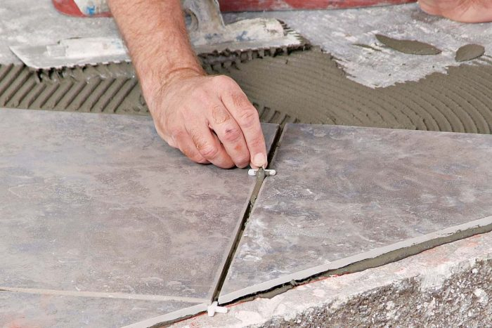 Use a tile spacer to remove excess wet thinset from between newly set tiles.