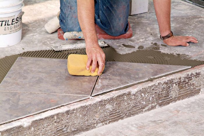 Clean up wet thinset drips from the face of the tiles with a damp sponge.