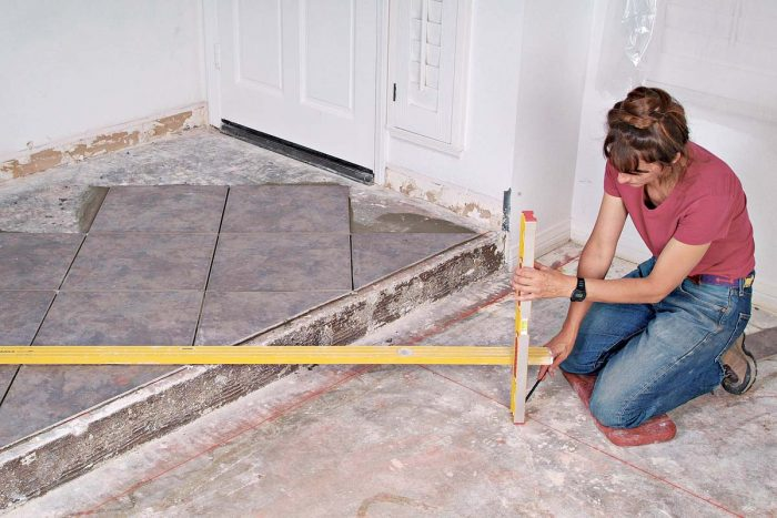 A long and a short level are used to transfer the layout lines from the entry area to the living/dining room floor.
