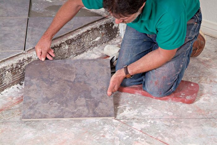 To maintain an even pattern across the stair step, the first tile on the lower level must be trimmed.