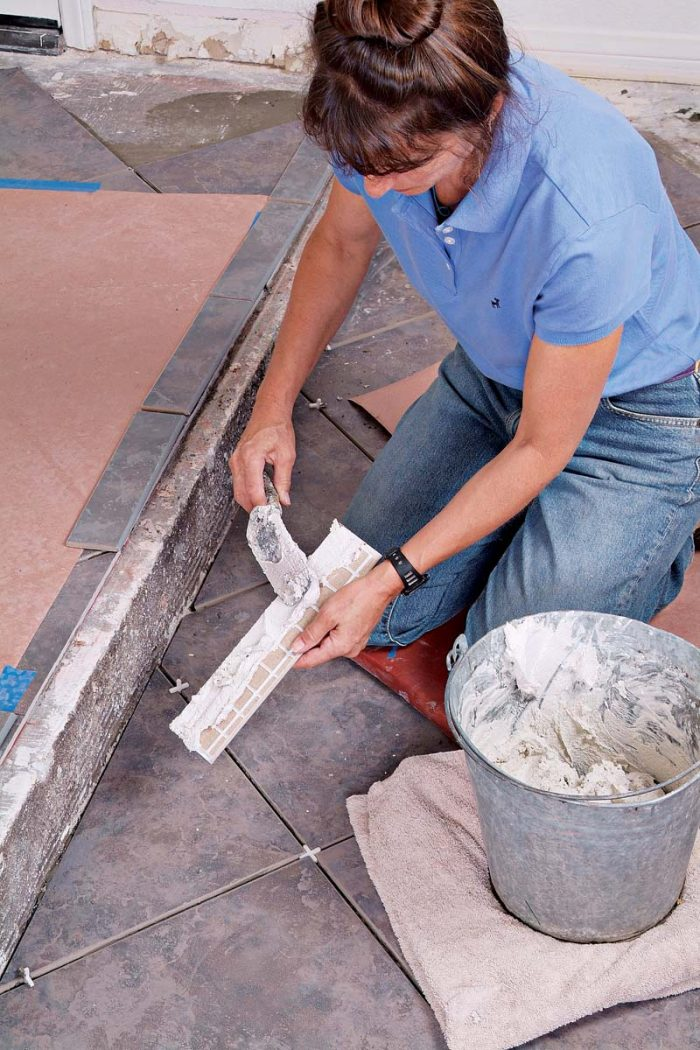 Back-buttering each bullnose trim tile ensures that its bond with the concrete floor will be strong.