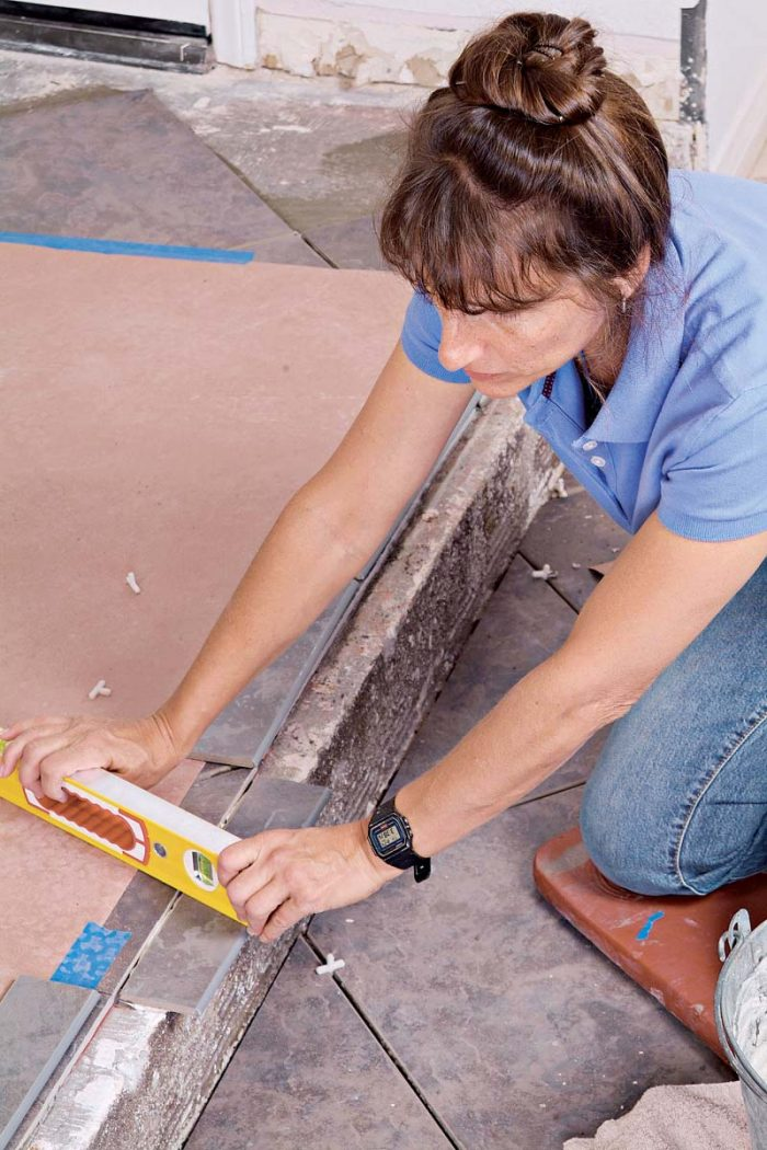 Use a small level to keep the bullnose tiles flat and even with the adjacent flooring.