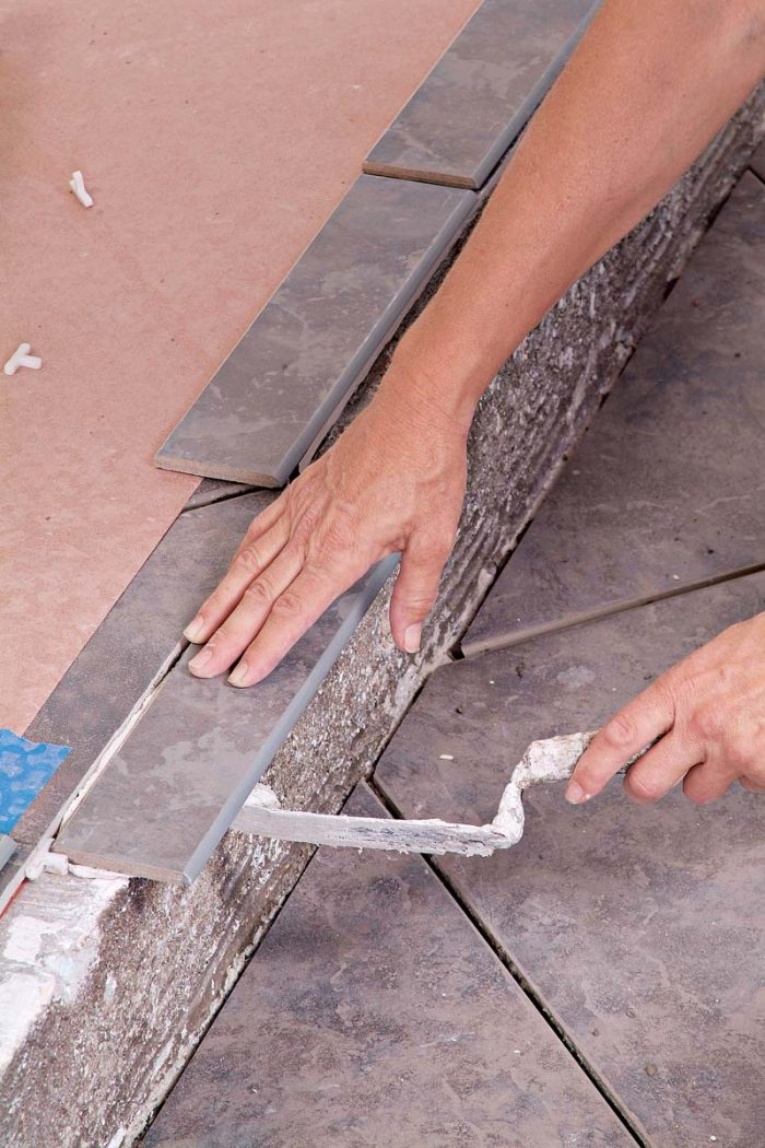 Use a margin trowel to remove excess thinset from the overhanging edge of the trim tiles.