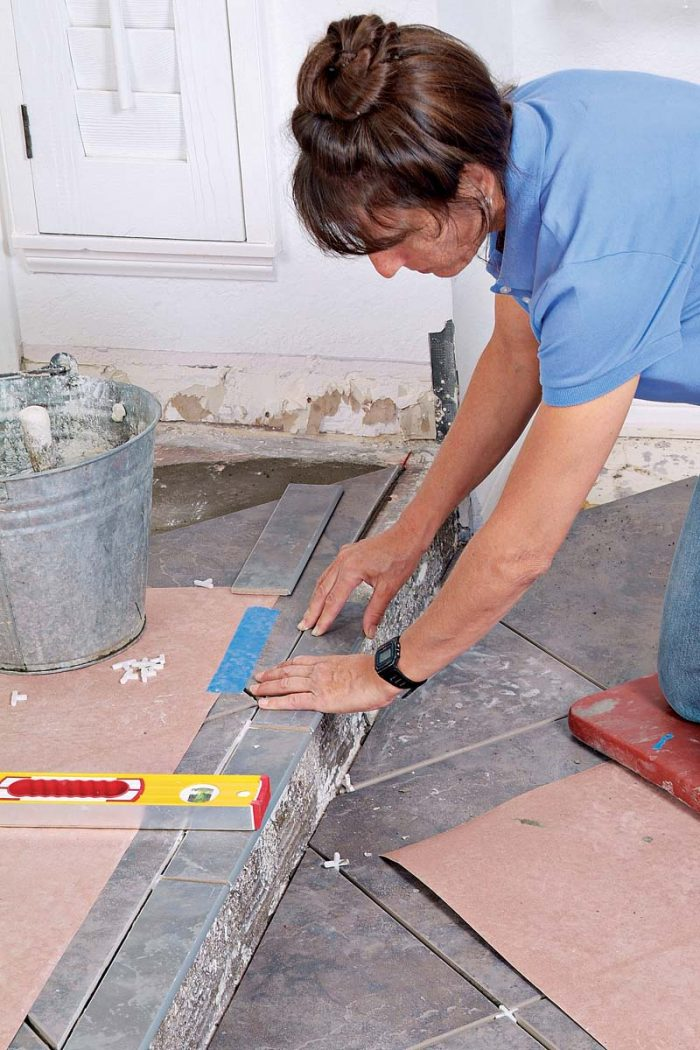 Continue down the edge of the step, setting the bullnose tiles level with one another and adding spacers as you go.