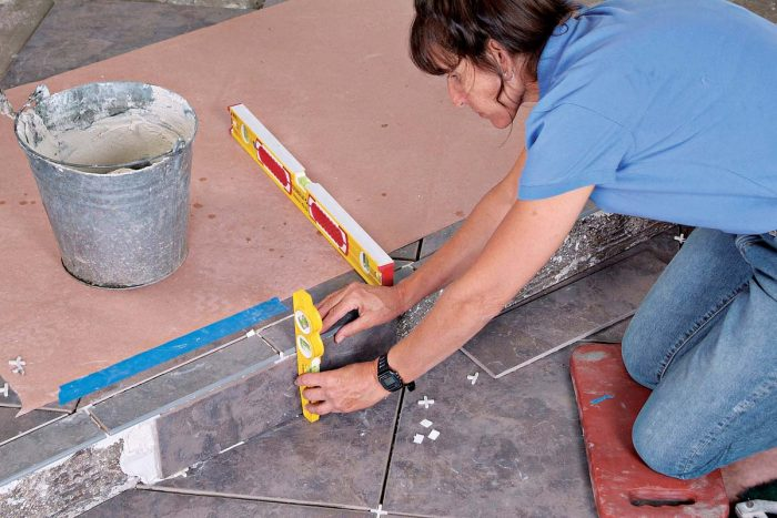 Use a torpedo level to make sure that the riser tiles are plumb and even with the edge of the bullnose tiles.