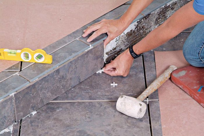 Place spacers and/or wedges under the riser tiles to adjust the grout joint at the top and form a caulk joint at the bottom.