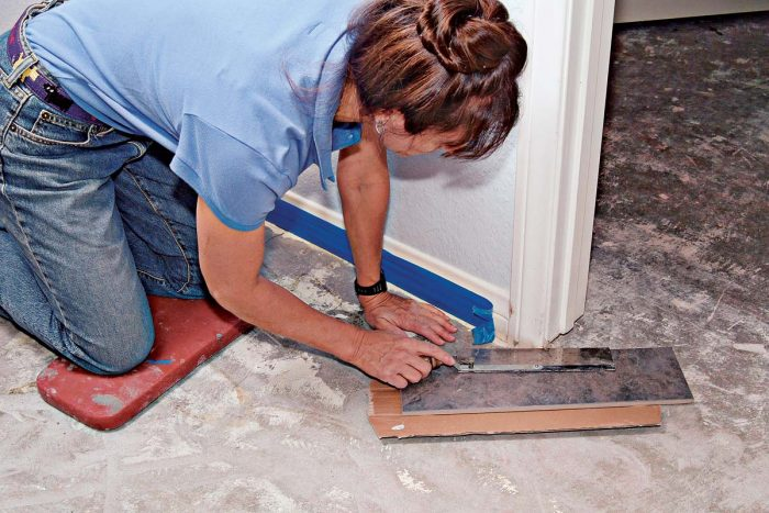 To set tile around doorways, first cut off the door casing, using a scrap tile, wood, or cardboard shim to support the saw.