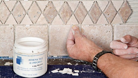 Insert wedges to help maintain an even grout joint.