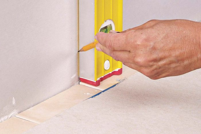A plumb line drawn on the wall helps you line up the grout joints of the backsplash tiles with the tiles on the countertop.