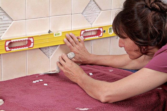 Check each row of tiles for level. Lift any low tiles with a margin trowel, then insert wedges to keep the tile in place.