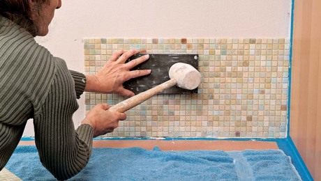 Strike your beater block gently and evenly to embed the mosaic tiles in place.