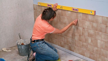 Continue tiling up the wall, checking every few rows with a level, and adjusting with spacers.